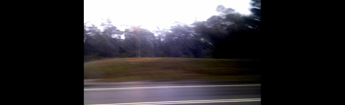 A photo of rain out the car window while on the road.